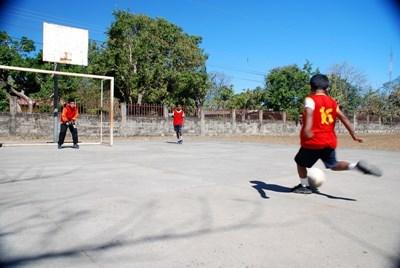 Student scores a goal during soccer practice with a volunteer coach in Costa Rica