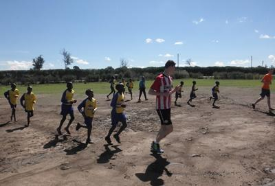 Kenyan school children participate in exercise drills with volunteers before soccer practice