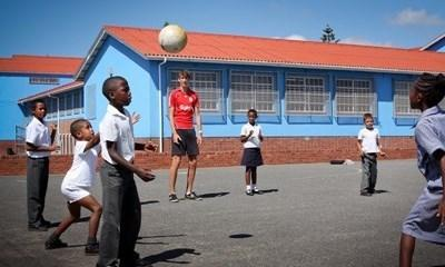 Volunteer sports coach instructing children at a school in South Africa
