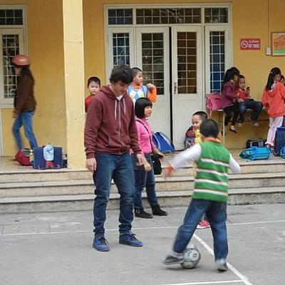 Sports volunteer does warm up activities with school children in Vietnam