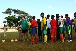 Children practice soccer skills with a volunteer during a physical education class in Jamaica.