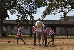 Physical education teaching volunteers play soccer with local high school students in Tanzania.