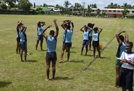 A group of young athletes stretch before a track and field event at a sports volunteer placement in Sri Lanka.
