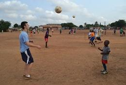 A volunteer teaches a young child to play soccer in a rural village abroad.
