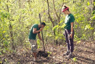 Projects Abroad volunteer and staff dig a hole to plant a tree sapling at the Barra Honda National Park in Costa Rica.