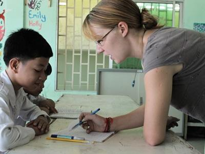 A volunteer teaches her young student English in Cambodia