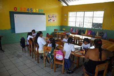 Students completing worksheets with volunteer teacher in a school in Ecuador