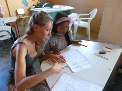 A young Ecuadorian student gets help from a Teaching volunteer