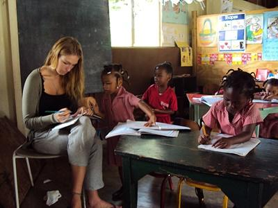 Volunteer correct students work in a school in Jamaica on the Teaching project