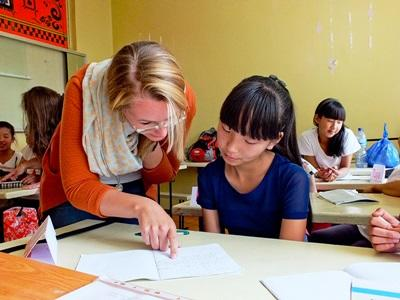 A child at a school in Mongolia gets some help from a Teaching volunteer
