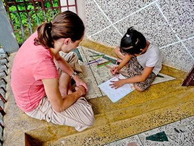 A Teaching volunteer does arets & crafts with a school child in Nepal, Asia
