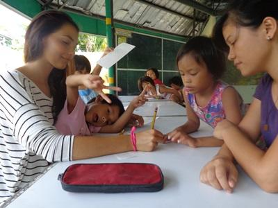 Teaching volunteer works with school children in a tutoring session in the Philippines