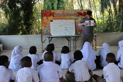 A group of children listen intently to a volunteer teacher as he teaches an English class.