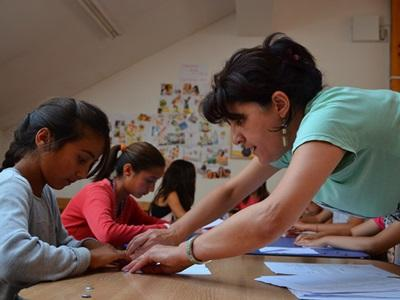 A young child in Romania gets help with school work from a volunteer.