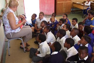 An older volunteer teaches a class of young children at a school in South Africa
