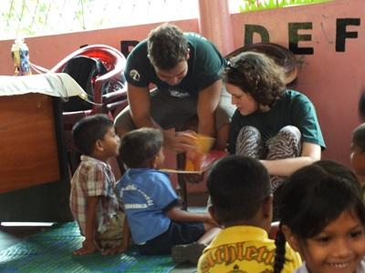 A male and female volunteer help each other teach Sri Lankan children