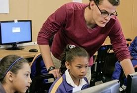 An IT teaching volunteer explains how to use Internet browsers at a school in South Africa.
