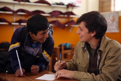 Teach Abroad: Projects Abroad volunteer assists a local student at a school in a developing country