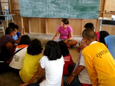 A volunteer leads an English lesson in a school with Thai children