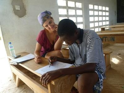 Volunteer tutors a man in French on a Teaching project in Togo