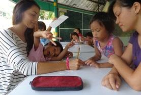 A teaching volunteer in the Philippines works with students on an activity.