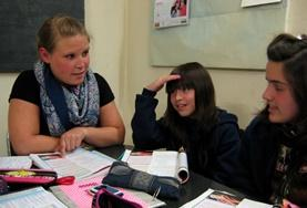 A volunteer helps teenagers in Argentina improve their French conversation skills.