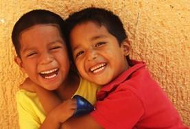 Two young students laugh and play at a placement on the Teach English and Other Subjects Project in Belize.