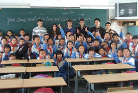 Volunteers teach English to a large group of students in China.