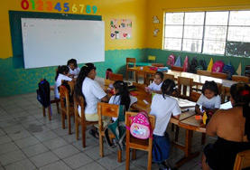 A volunteer teaches children at a school in Ecuador.