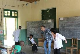 A volunteer teaches a class in Madagascar with the help of a local teacher.