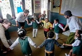 A group of children participate in a classroom activity with teaching volunteers in Nepal.