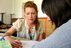 A volunteer teacher helps a student with her English at a high school in Romania.