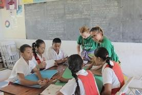 A group of students practice their English with teaching volunteers at a school in Samoa.