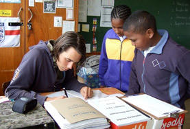 A teaching volunteer helps two students with an activity during class in South Africa.