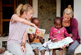 Children listen to stories read aloud by volunteers teaching in Tanzania.