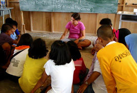 A volunteer teacher in Thailand helps a young boy with his classwork.