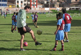 A volunteer coaches sport to young students in Asia.