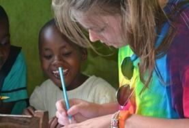 A volunteer on a Care & Community Winter Break Trip helps a child complete an activity at a school in Ghana.