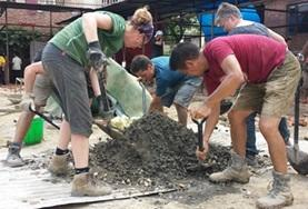 A group of volunteers shovel sand to make cement at the Building Project in Nepal.
