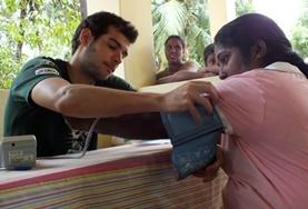 A medical volunteer checks blood pressure at an outreach in Sri Lanka during his Winter Break Trip.