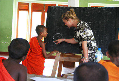 A Projects Abroad volunteer teaches students in Sri Lanka how to tell time in English.